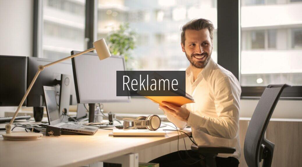 En smilende mand ved et skrivebord